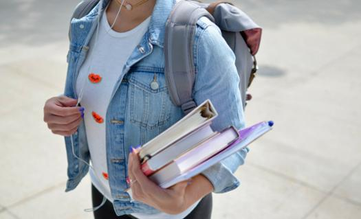 student carrying binders and books