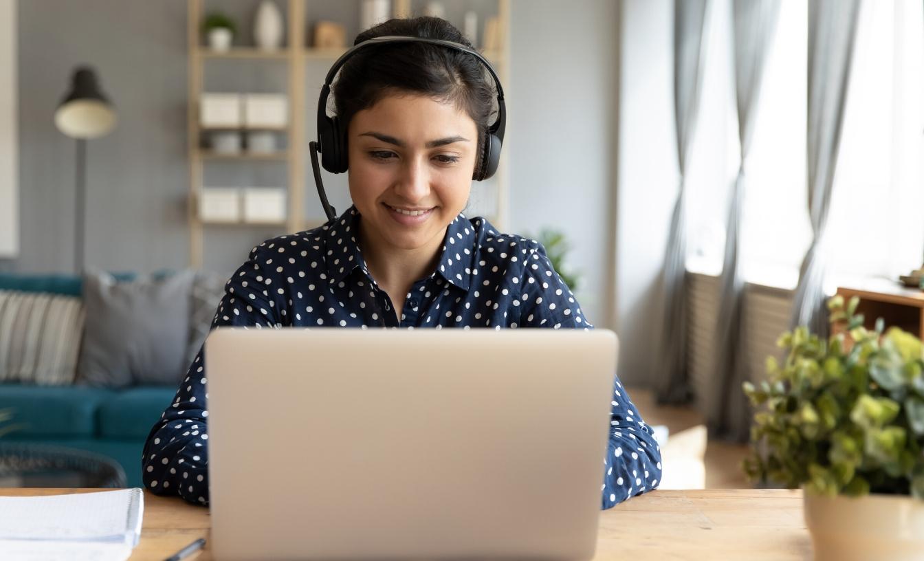 Une femme portant un casque est assise devant son ordinateur portable.