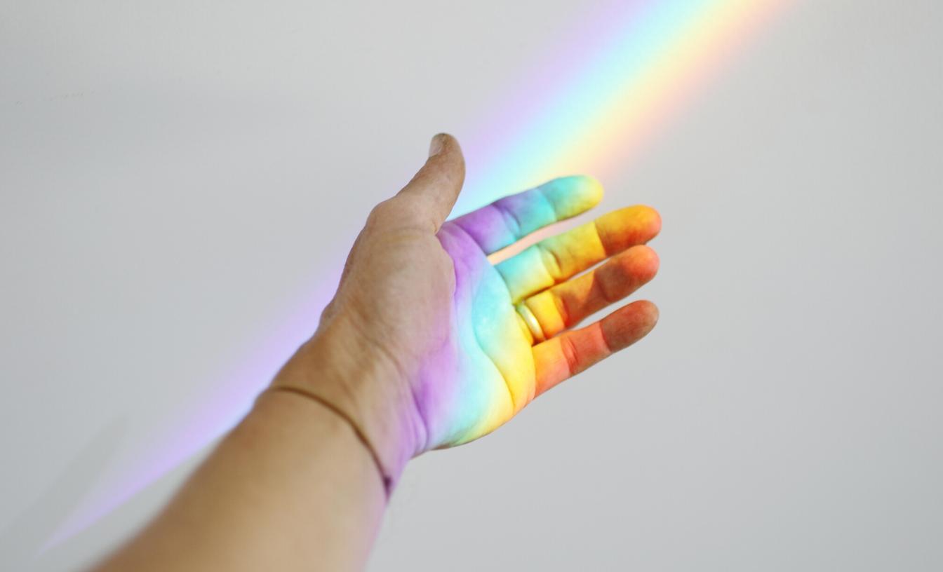 Une main tendue avec un rayon de soleil arc-en-ciel la recouvrant.