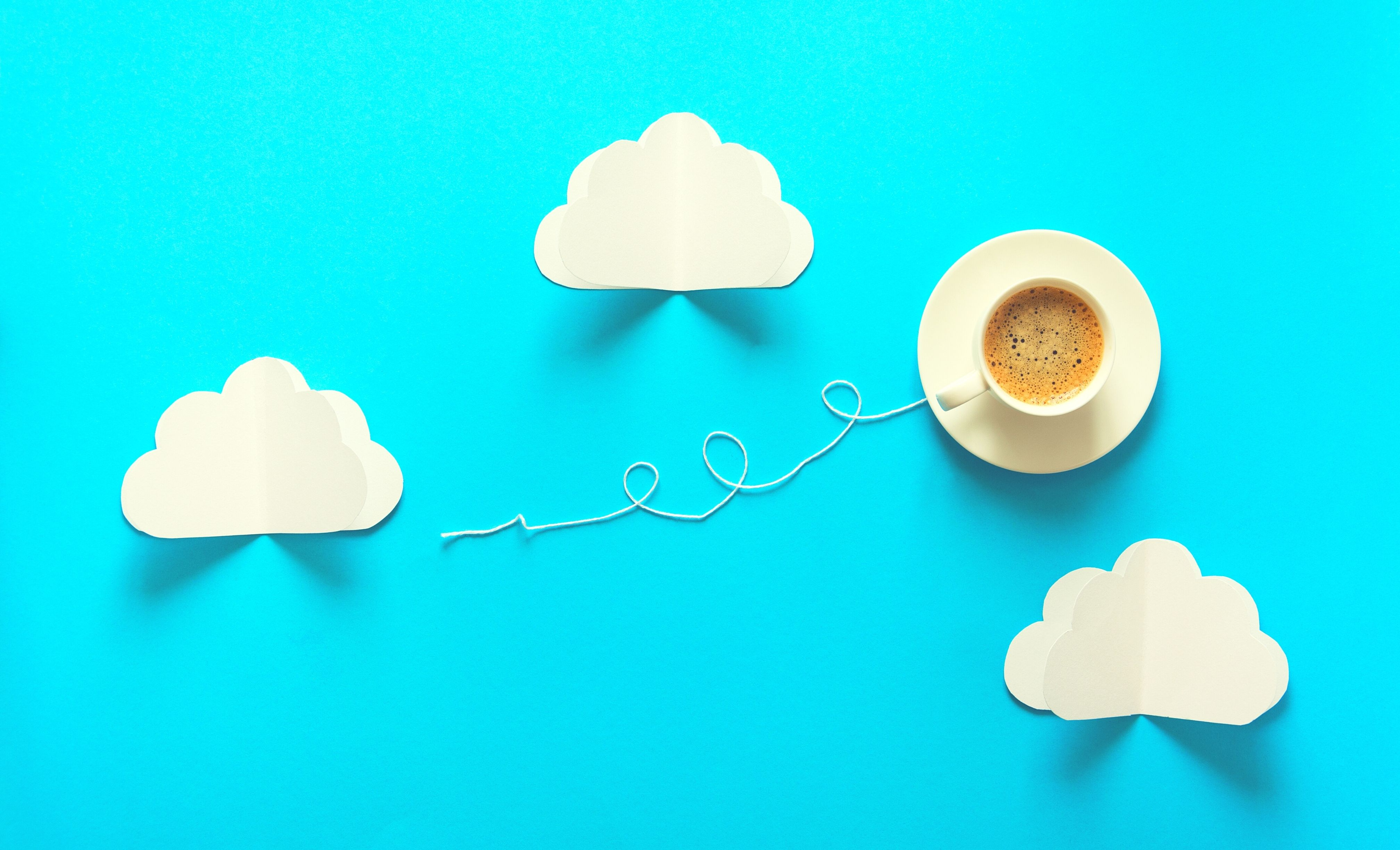 A cup of coffee, surrounded by several paper clouds. There is a string attached to the cup to give the impression that it's a kite.